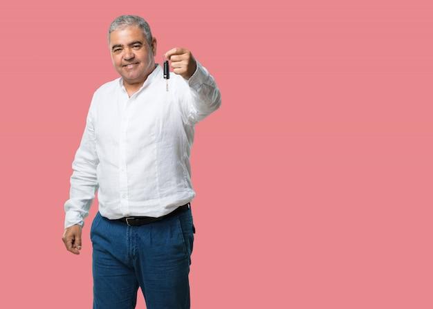 Meio envelhecido homem feliz e sorridente, segurando as chaves do carro