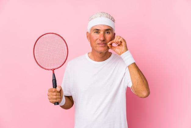 Meio envelhecido homem jogando badminton isolado com os dedos nos lábios, mantendo um segredo.