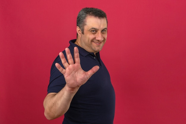Meio envelhecido homem vestindo camisa polo com sorriso no rosto e mostrando o número cinco com os dedos sobre parede rosa isolada