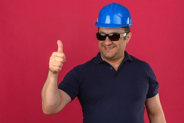 Meio envelhecido homem vestindo camisa polo e capacete de segurança aparecendo polegares com sorriso no rosto sobre parede rosa isolada