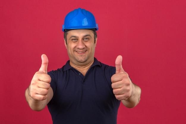 Meio envelhecido homem vestindo camisa polo e capacete de segurança com sorriso no rosto e aparecendo os polegares sobre parede rosa isolada