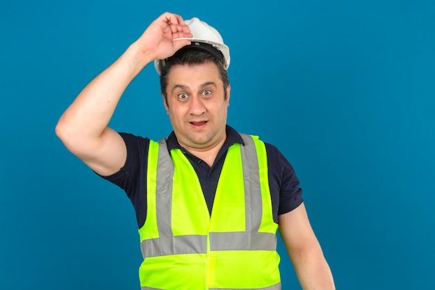 Meio envelhecido homem vestindo construção colete amarelo e capacete de segurança olhando surpreso tocando seu capacete sobre parede azul isolada