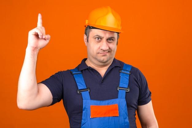 Meio envelhecido homem vestindo uniforme de construção e capacete de segurança, apontando o dedo descontente e frustrado sobre parede laranja isolada