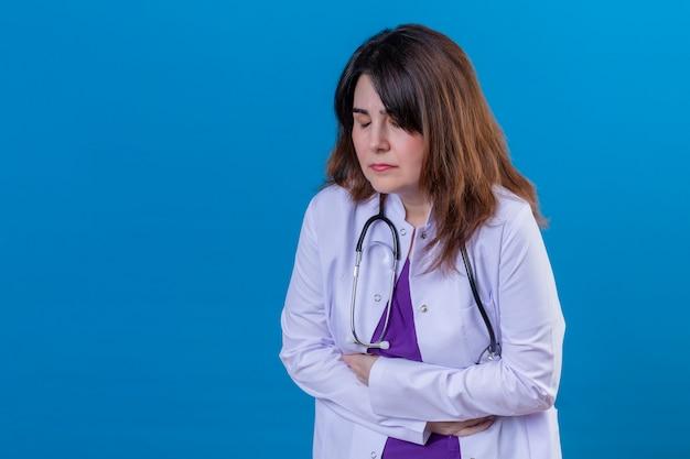 Meio envelhecido médico vestindo jaleco branco e com estetoscópio olhando indisposto tocar o estômago sofrendo de dor ao longo da parede azul