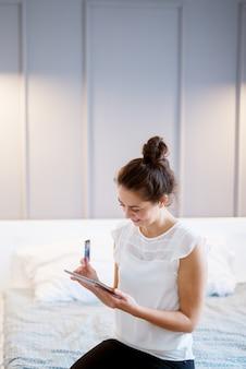 Meio envelhecido mulher às compras no tablet no quarto.