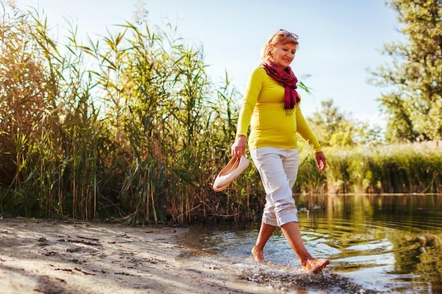 Meio, envelhecido, mulher caminhando, ligado, rio, banco, ligado, outono, dia sênior, senhora, tendo divertimento