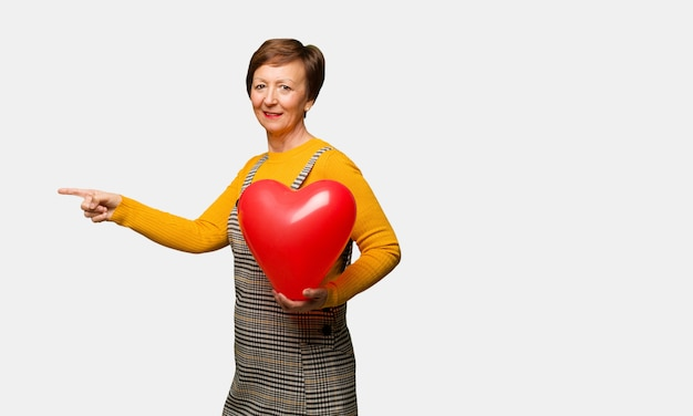 Meio envelhecido mulher comemorando o dia dos namorados, apontando para o lado com o dedo
