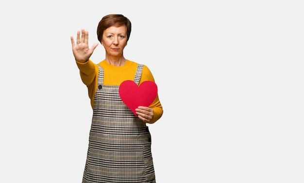 Meio envelhecido mulher comemorando o dia dos namorados, colocando a mão na frente