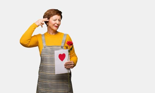 Meio envelhecido mulher comemorando o dia dos namorados fazendo um gesto de suicídio