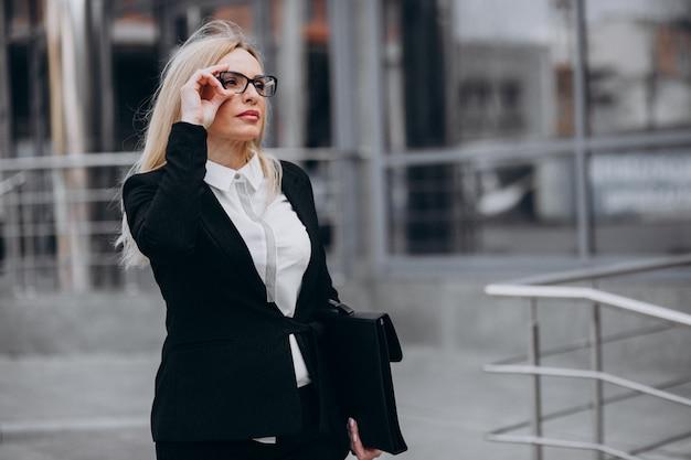 Meio envelhecido mulher de negócios com mala pelo centro de negócios