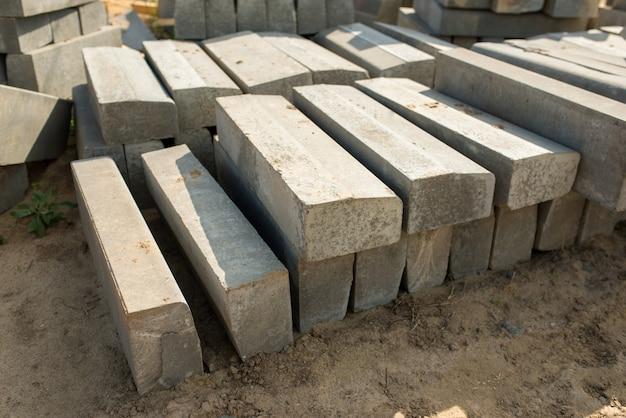 Meio-fio de concreto empilhados em um canteiro de obras