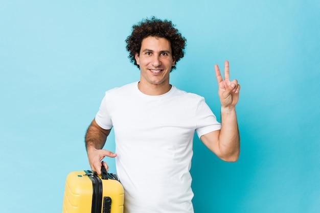 Meio jovem homem segurando uma mala mostrando sinal de vitória e sorrindo amplamente.