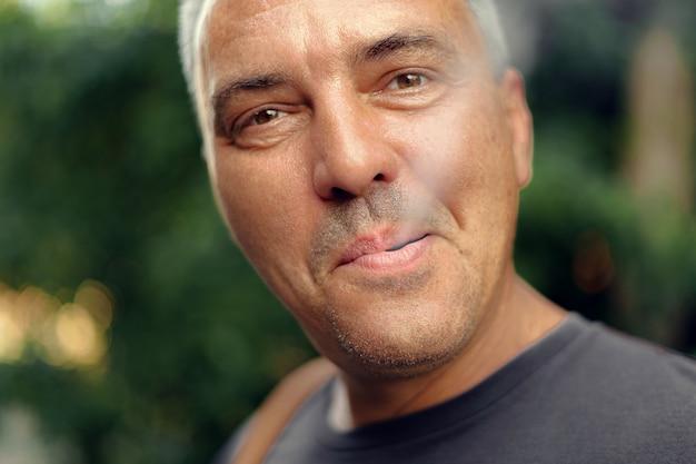 Meio maduro caucasiano cigarro de fumo envelhecido do homem ao ar livre. dependência de nicotina. copie o espaço