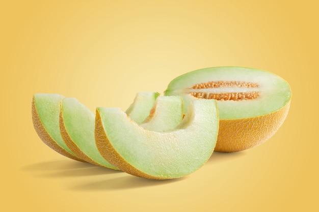 Meio melão e três fatias em fundo amarelo, conceito de verão