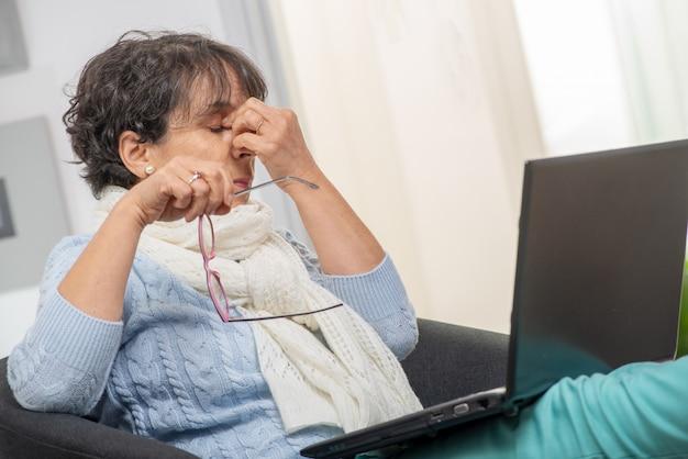 Meio mulher envelhecida com estressado, esfregando os olhos
