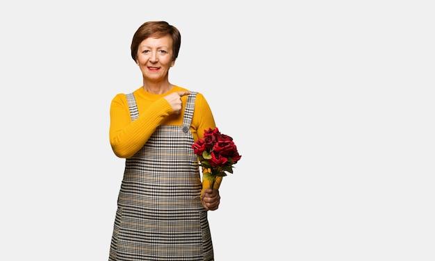Meio mulher envelhecida comemorando o dia dos namorados sorrindo e apontando para o lado