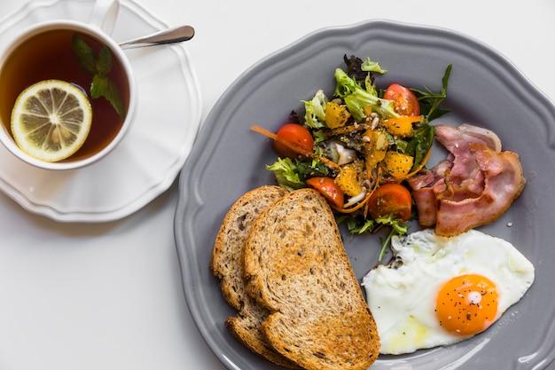 Meio ovo frito; torrada; salada; bacon na placa cinza com limão e hortelã xícara de chá no fundo branco