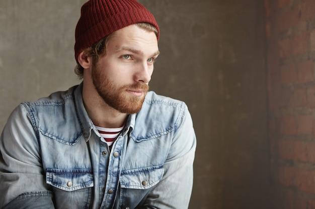 Meio perfil de hipster bonito com barba, vestida com roupas da moda, com olhar pensativo, à espera de alguém no café, sentado contra a parede de concreto