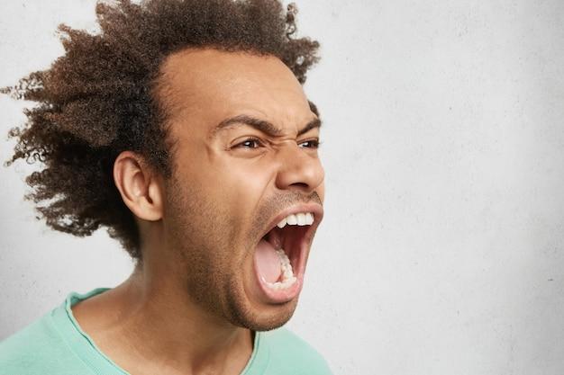 Meio perfil de homem agressivo com cabelo escuro e encaracolado, abre a boca amplamente, grita em pânico