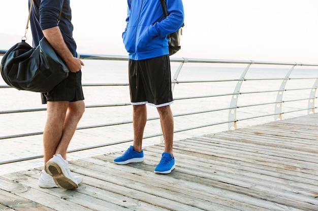 Meio retrato de dois jovens desportistas ao ar livre na praia, a conversar