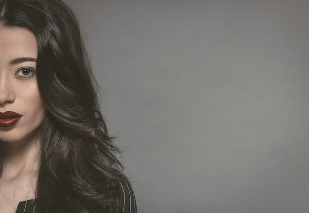Meio retrato de uma bela jovem com lindos cabelos longos e escuros olhando para a frente, isolado na parede cinza