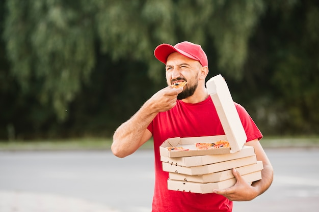 Meio tiro cara de entrega comendo pizza