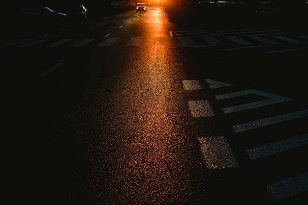 Meio urbano de uma rua escura ao entardecer com carros e marcas de tráfego