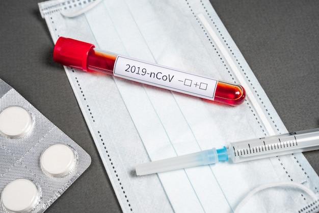 Meios para o tratamento e prevenção de coronavírus - uma máscara médica descartável, medicamentos antipiréticos e antivirais.