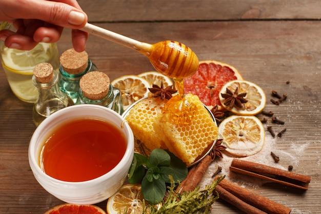 Mel, canela e frutas secas em uma mesa de madeira. alimentação saudável.