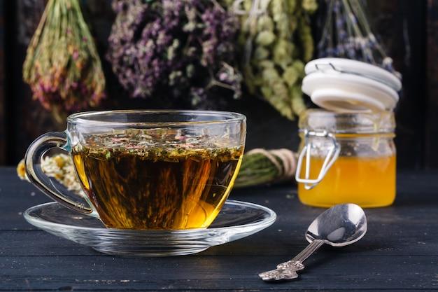 Mel com chá na mesa rústica backgound com ervas