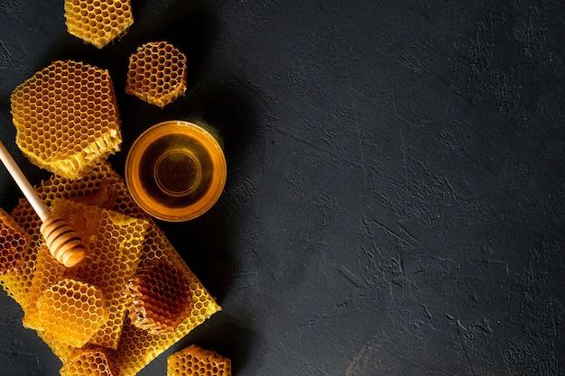Mel com favo de mel na mesa preta, vista superior. espaço para texto