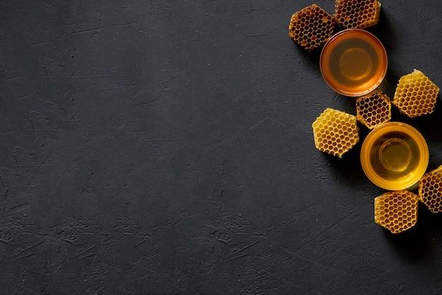 Mel com favo de mel na mesa preta, vista superior. espaço para texto.