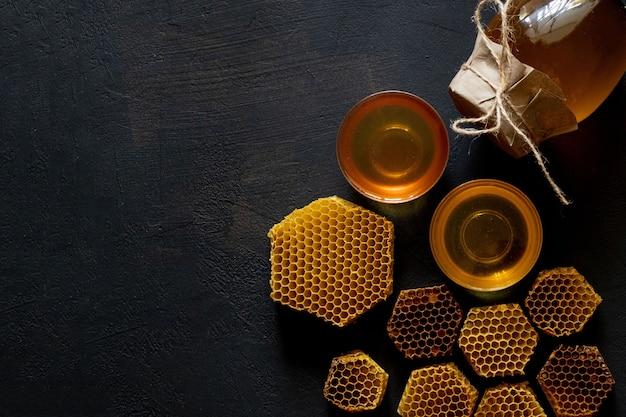 Mel com favo de mel na mesa preta
