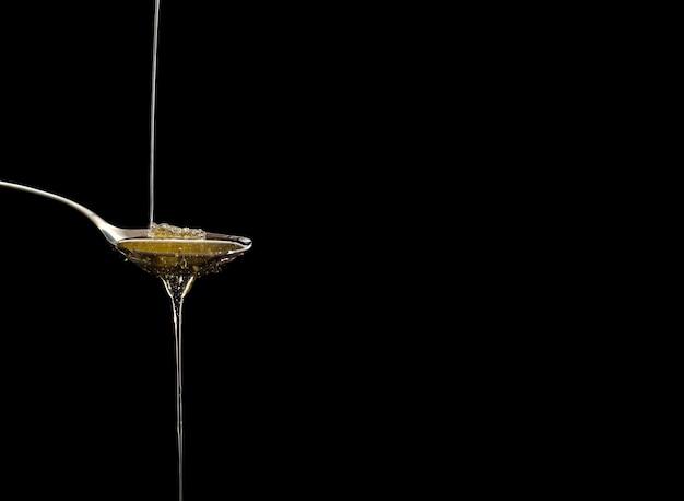 Mel cru orgânico na colher com gotas do mel, bondade doce natural pura