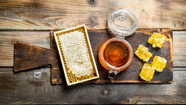 Mel de abelha em uma velha placa. sobre um fundo de madeira.