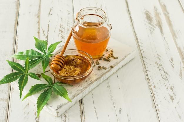 Mel de cannabis em uma tigela com sementes de madeira mais profundas, cânhamo leawes amd na mesa de madeira.