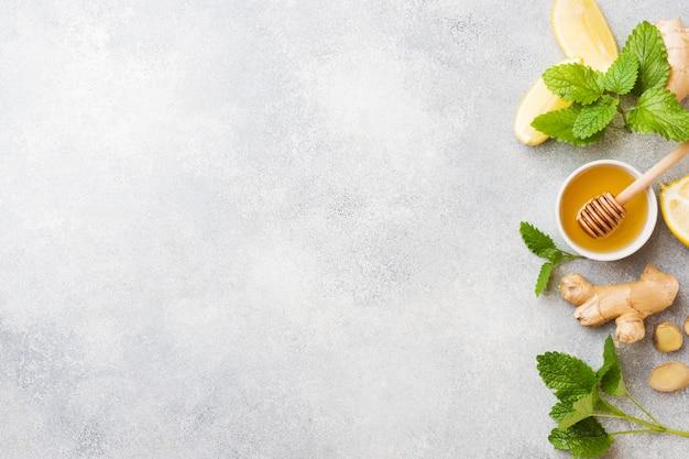 Mel de limão e gengibre raiz de hortelã na superfície cinza