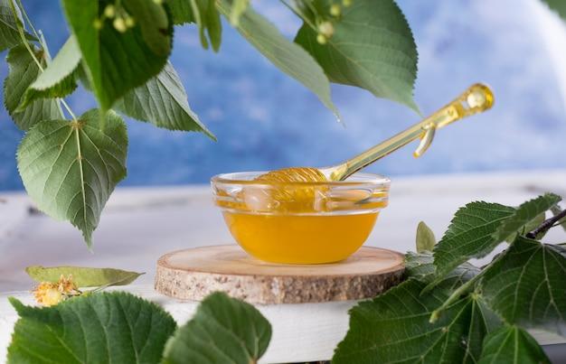 Mel de tília em pote e tigela com uma concha de mel em uma mesa de madeira branca