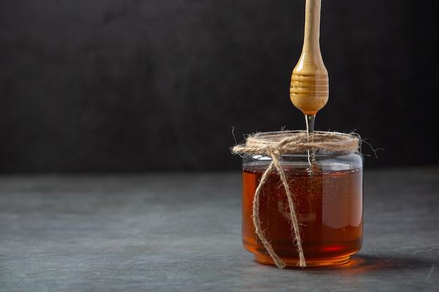 Mel delicioso com concha de mel de madeira em superfície escura