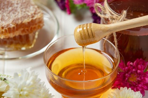 Mel delicioso com concha de mel de madeira na superfície de madeira branca