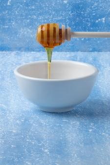 Mel delicioso e natural na tigela branca.