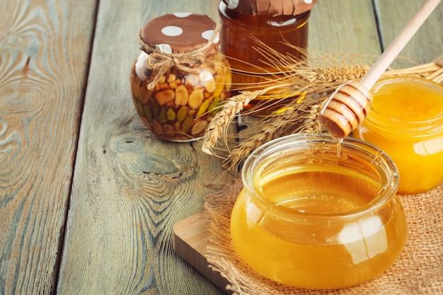 Mel doce mel em frasco de vidro na superfície de madeira
