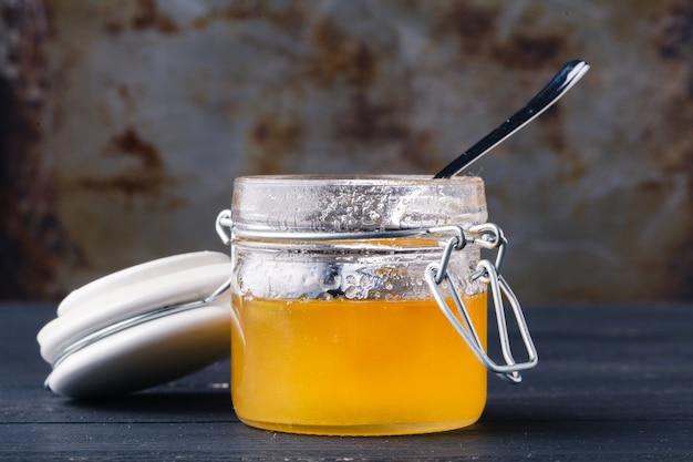 Mel dourado em frasco de vidro na mesa rústica