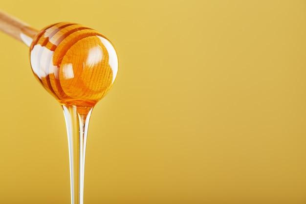 Mel dourado escorre de uma concha de mel de madeira em um fundo amarelo