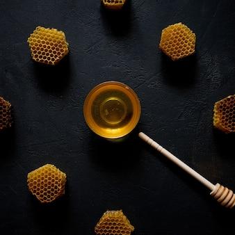 Mel e favo de mel na forma de um relógio na mesa preta, vista superior.