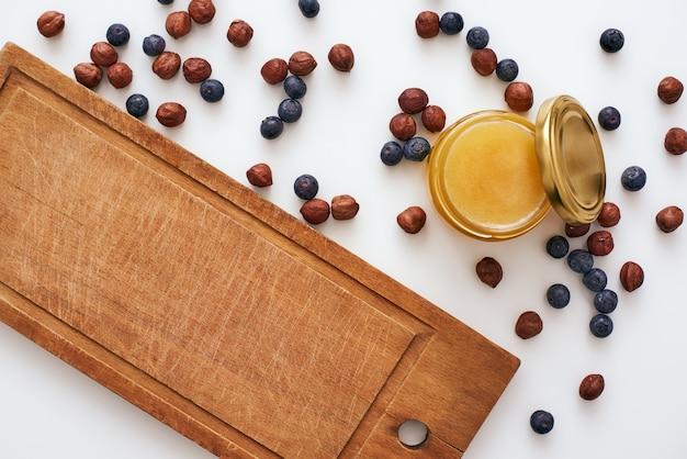 Mel e frutas secas estão espalhadas na mesa