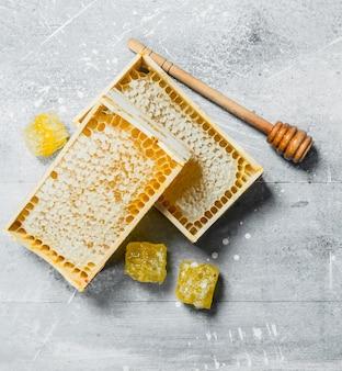 Mel em favos de mel de madeira. em um rústico.