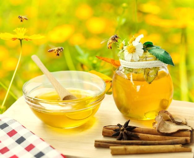 Mel em frasco de vidro com abelha voando e flores no chão de madeira