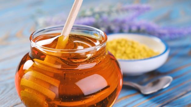 Mel em frasco de vidro com concha de mel sobre fundo de madeira com favo de mel e própolis, xarope de açúcar líquido, néctar de flor