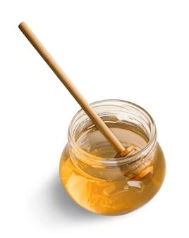 Mel em frasco de vidro e concha de mel